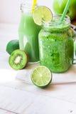 Caneca do frasco de pedreiro com o batido do legume fresco, garrafa com suco de fruto verde, maçãs dos ingredientes, citrino, qui Imagem de Stock Royalty Free