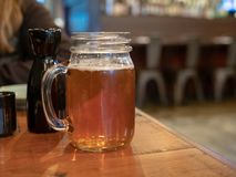 Caneca do frasco de pedreiro com o punho enchido com a cerveja ao lado da garrafa da causa no restaurante imagem de stock