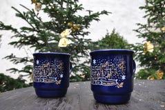 A caneca do Natal de dois azuis com uma imagem está na tabela de madeira Fotografia de Stock Royalty Free