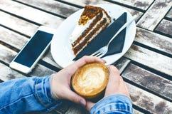 Caneca e bolo de café em uma tabela de madeira do vintage Conceito do moderno Bebida da mulher um café Copos do americano e do ma Imagem de Stock Royalty Free