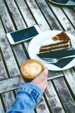 Caneca e bolo de café em uma tabela de madeira do vintage Conceito do moderno Bebida da mulher um café Copos do americano e do ma Imagem de Stock