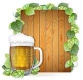 Caneca e lúpulos de cerveja em um fundo de madeira Fotografia de Stock Royalty Free