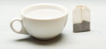 A caneca encheu-se com a água a ferver e o saquinho de chá no fundo branco Conceito do tempo do chá Processo de chá que fabrica c Imagens de Stock