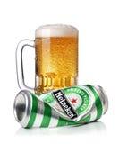 Caneca gelado de cerveja e de lata de cerveja amarrotada de Heineken com gotas da água, isolada em um fundo branco Fotografia de Stock Royalty Free