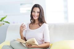 Caneca guardando moreno bonita de sorriso e leitura de um livro ao relaxar no sofá imagens de stock