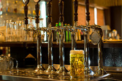 A caneca para cerveja da cerveja com cerveja bate em um bar Fotografia de Stock Royalty Free