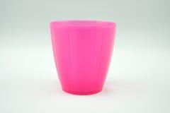 Caneca plástica cor-de-rosa no fundo branco Fotos de Stock Royalty Free