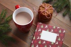 Caneca vermelha de cacau, de livro de Natal e de pilha das cookies na tabela de madeira Imagem de Stock Royalty Free