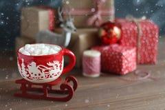 Caneca vermelha do Natal com os marshmallows no pequeno trenó vermelho pequeno Imagens de Stock