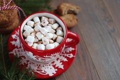 Caneca vermelha do Natal de café e marshmallows e cookies na tabela de madeira Fotografia de Stock