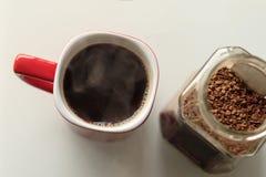 Caneca vermelha o café é derramado nele É um vapor verdadeiro ao lado do frasco de vidro, os grânulo do café são abertos nele fotografia de stock royalty free