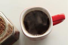 Caneca vermelha o café é derramado nele É um vapor verdadeiro ao lado do frasco de vidro, os grânulo do café são abertos nele imagem de stock royalty free