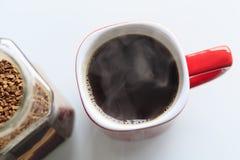Caneca vermelha o café é derramado nele É um vapor verdadeiro ao lado do frasco de vidro, os grânulo do café são abertos nele fotos de stock royalty free