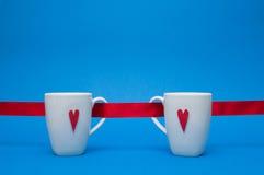 Canecas com corações e a fita vermelhos Imagem de Stock