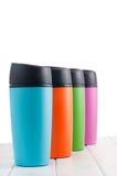 Canecas da garrafa térmica da cor na tabela branca Imagem de Stock Royalty Free