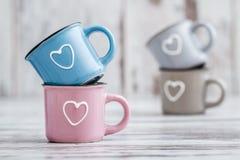 Canecas de café bonitos coloridas com corações Imagens de Stock