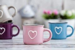 Canecas de café bonitos coloridas com corações Fotografia de Stock Royalty Free