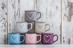 Canecas de café bonitos coloridas com corações Imagem de Stock