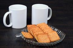 Canecas de café branco com os biscoitos na placa de vidro Fotografia de Stock