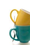 Canecas de café coloridas com a colher de encontro ao branco Fotos de Stock