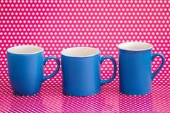 Canecas de café coloridas no fundo cor-de-rosa com pontos brancos Imagem de Stock Royalty Free