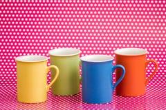 Canecas de café coloridas no fundo cor-de-rosa com pontos brancos Imagem de Stock