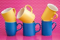Canecas de café coloridas no fundo cor-de-rosa com pontos brancos Foto de Stock Royalty Free