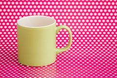 Canecas de café coloridas no fundo cor-de-rosa com pontos brancos Fotografia de Stock Royalty Free