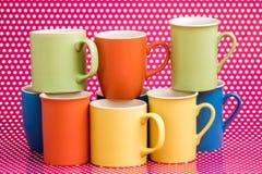 Canecas de café coloridas no fundo cor-de-rosa com pontos brancos Imagens de Stock Royalty Free