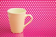 Canecas de café coloridas no fundo cor-de-rosa com pontos brancos Fotos de Stock Royalty Free