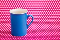 Canecas de café coloridas no fundo cor-de-rosa com pontos brancos Imagens de Stock