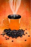 Canecas de café e feijões de café alaranjados Imagens de Stock Royalty Free