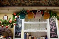 Canecas de café que penduram sobre o contador no café acolhedor Imagens de Stock Royalty Free