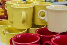 Canecas de café vermelhas, brancas, e amarelas Imagem de Stock