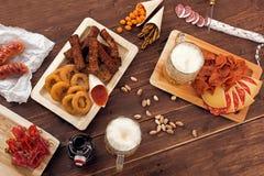 Canecas de cerveja com petiscos Imagens de Stock