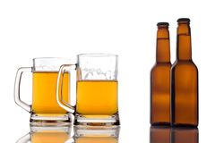Canecas de cerveja e dois frascos da cerveja Imagens de Stock Royalty Free