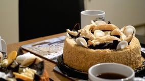 Canecas dos copos de chá com as duas galdérias do bolo da sobremesa na tabela de madeira em casa Foto de Stock