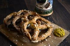 Caneco de cerveja e mostarda alemães da cerveja dos petiscos dos pretzeis na madeira Foto de Stock Royalty Free