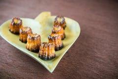 Canelé de los pasteles franceses en una placa fotografía de archivo libre de regalías