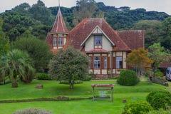 CANELA BRASILIEN - MAJ 06, 2016: trevlig forntida byggnad med en stor framdelträdgård med lotten av träd och gräs Royaltyfri Bild