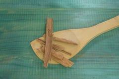 Canela, cuchara de madera, en fondo de madera verde Fotos de archivo libres de regalías
