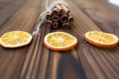 Canela, naranjas secadas y anís en la tabla de madera marrón Fotos de archivo