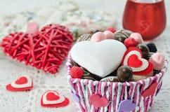Canestro con il cioccolato, i biscotti ed i cuori decorativi di un giorno di biglietti di S. Valentino Immagine Stock