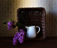 Canestro con il lillà e un bicchiere d'acqua Fotografie Stock