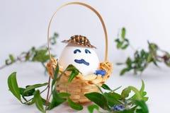 Canestro con l'uovo di Pasqua con i baffi in un ramo dell'erba verde e del cappello su fondo pastello bianco Idea creativa Concet immagini stock