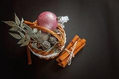 Canestro con le decorazioni di Natale su fondo nero Fotografie Stock Libere da Diritti