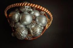 Canestro con le decorazioni di Natale su fondo nero Fotografie Stock