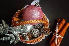 Canestro con le decorazioni di Natale su fondo nero Immagine Stock