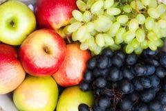 Canestro con le mele di autunno ed il primo piano blu e verde dell'uva Struttura dell'uva autunnale e dell'uva Il concetto di rac fotografia stock libera da diritti