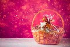 Canestro con le particelle festive, fondo porpora del regalo fotografie stock